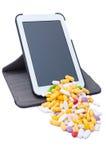 Píldoras coloreadas que vienen de la tableta inalámbrica Fotos de archivo libres de regalías