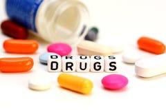 Píldoras coloreadas y palabra de las drogas aislada en el fondo blanco Imagenes de archivo