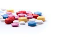 Píldoras coloridas de la medicina en el fondo blanco Imagen de archivo