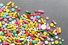 Píldoras coloridas de la medicina en fondo gris Foto de archivo libre de regalías
