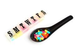 Píldoras coloridas en la cuchara de cerámica con la medicina diaria de la caja Fotografía de archivo libre de regalías
