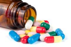 Píldoras coloridas en una botella de cristal aislada en el fondo blanco Foto de archivo libre de regalías