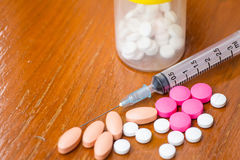 Píldoras con la caja y la jeringuilla de la medicina en la tabla de madera Imagenes de archivo