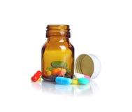 Píldoras de la botella de píldora que se derraman fuera de la botella de píldora Fotografía de archivo
