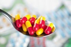 Píldoras de la cápsula en cuchara Imágenes de archivo libres de regalías