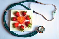 Píldoras de la cápsula en la placa blanca con el stetoscop Imágenes de archivo libres de regalías