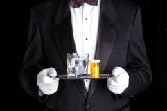 Píldoras de la explotación agrícola del hombre y vidrio de agua en la bandeja de plata Foto de archivo libre de regalías