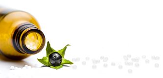 Píldoras de la homeopatía con la belladona aislada foto de archivo