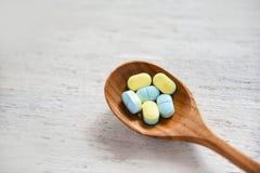 Píldoras de la medicina amarillas y azules en cuchara de madera en el fondo de madera blanco de la tabla en farmacia foto de archivo libre de regalías