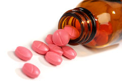 Píldoras de la medicina que desbordan una botella Fotos de archivo