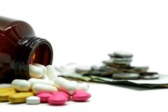 Píldoras de la medicina, vitaminas y botella en moneda borrosa del dinero y fondo blanco con el espacio de la copia foto de archivo