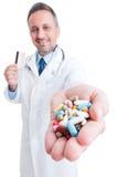 Píldoras de ofrecimiento del farmacéutico y sostener la tarjeta de crédito Fotos de archivo