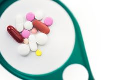 Píldoras debajo de una lupa en el fondo blanco foto de archivo