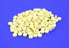 Píldoras del ácido fólico en fondo azul Foto de archivo