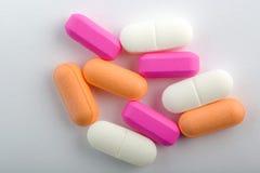 Píldoras del color en blanco Foto de archivo