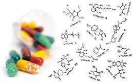 Píldoras del suplemento de la vitamina y fórmulas químicas Foto de archivo