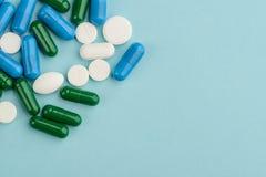 Píldoras derramadas sobre azul claro imagen de archivo libre de regalías