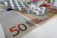 Píldoras e inyección en billete de banco euro - seguro imágenes de archivo libres de regalías