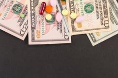 Píldoras en dólares con el copyspace negro Fotografía de archivo libre de regalías