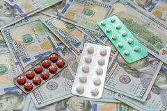 Píldoras en el dinero de 100 dólares Costos de la medicina Altos costes del concepto costoso de la medicación fotografía de archivo