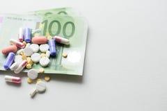 Píldoras en el dinero euro aislado en el fondo blanco Costos de la medicina Lugar para el texto imagen de archivo libre de regalías