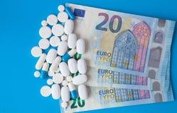 Píldoras en el dinero euro en fondo azul Costos de la medicina Altos costes del concepto de la medicación Cierre para arriba fotos de archivo libres de regalías