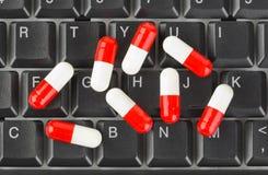 Píldoras en el teclado de ordenador Foto de archivo libre de regalías