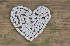 Píldoras en forma de un corazón Imagen de archivo libre de regalías