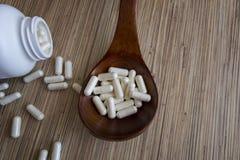Píldoras en la cuchara en un fondo de madera foto de archivo