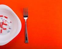 Píldoras en la placa con la fork Fotos de archivo