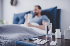 Píldoras en la tabla con el hombre enfermo en la cama fotos de archivo