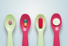Píldoras en las cucharas Fotos de archivo libres de regalías