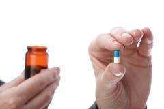 Píldoras en mano de la mujer Foto de archivo