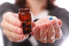 Píldoras en mano de la mujer Fotos de archivo libres de regalías