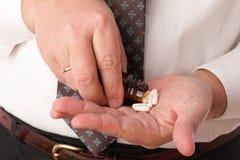 Píldoras en mano del hombre Foto de archivo