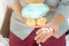 píldoras en mano mayor y sostener de la mujer el oso de peluche con la máscara en f Fotografía de archivo