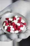 Píldoras en mano monocromática Foto de archivo libre de regalías