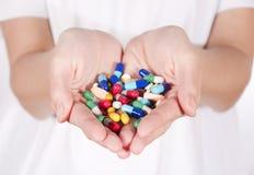 Píldoras en manos Fotos de archivo