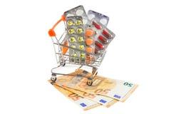 Píldoras en un carro de la compra con el dinero imagenes de archivo