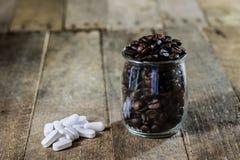 Píldoras en un envase y un café de plástico Granos de café en un vidrio Foto de archivo