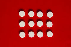 Píldoras en un fondo rojo Imágenes de archivo libres de regalías