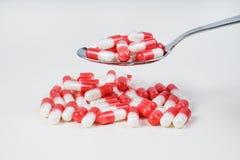 Píldoras en una cuchara imagen de archivo libre de regalías