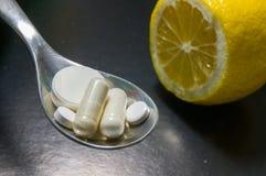 Píldoras en una cuchara contra el limón Imagenes de archivo