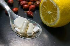 Píldoras en una cuchara contra el limón con las caderas Imagen de archivo
