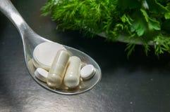 Píldoras en una cuchara contra verdes en la placa Imagen de archivo libre de regalías