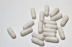 Píldoras en una superficie blanca imagenes de archivo