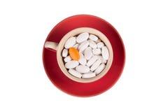 Píldoras en una taza en un platillo rojo fotografía de archivo
