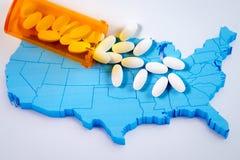 Píldoras farmacéuticas blancas que desbordan la botella de la prescripción sobre el mapa de América Fotografía de archivo libre de regalías