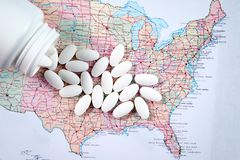 Píldoras farmacéuticas blancas que desbordan la botella de la prescripción sobre el mapa del fondo de América imagen de archivo