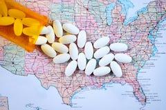 Píldoras farmacéuticas blancas que desbordan la botella de la prescripción sobre el mapa del fondo de América foto de archivo libre de regalías